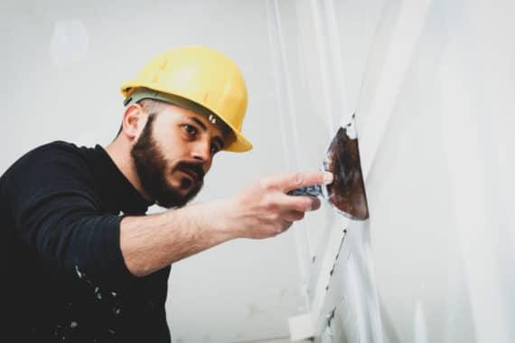 Pose de bandes calicot sur un nouveau mur en plâtre